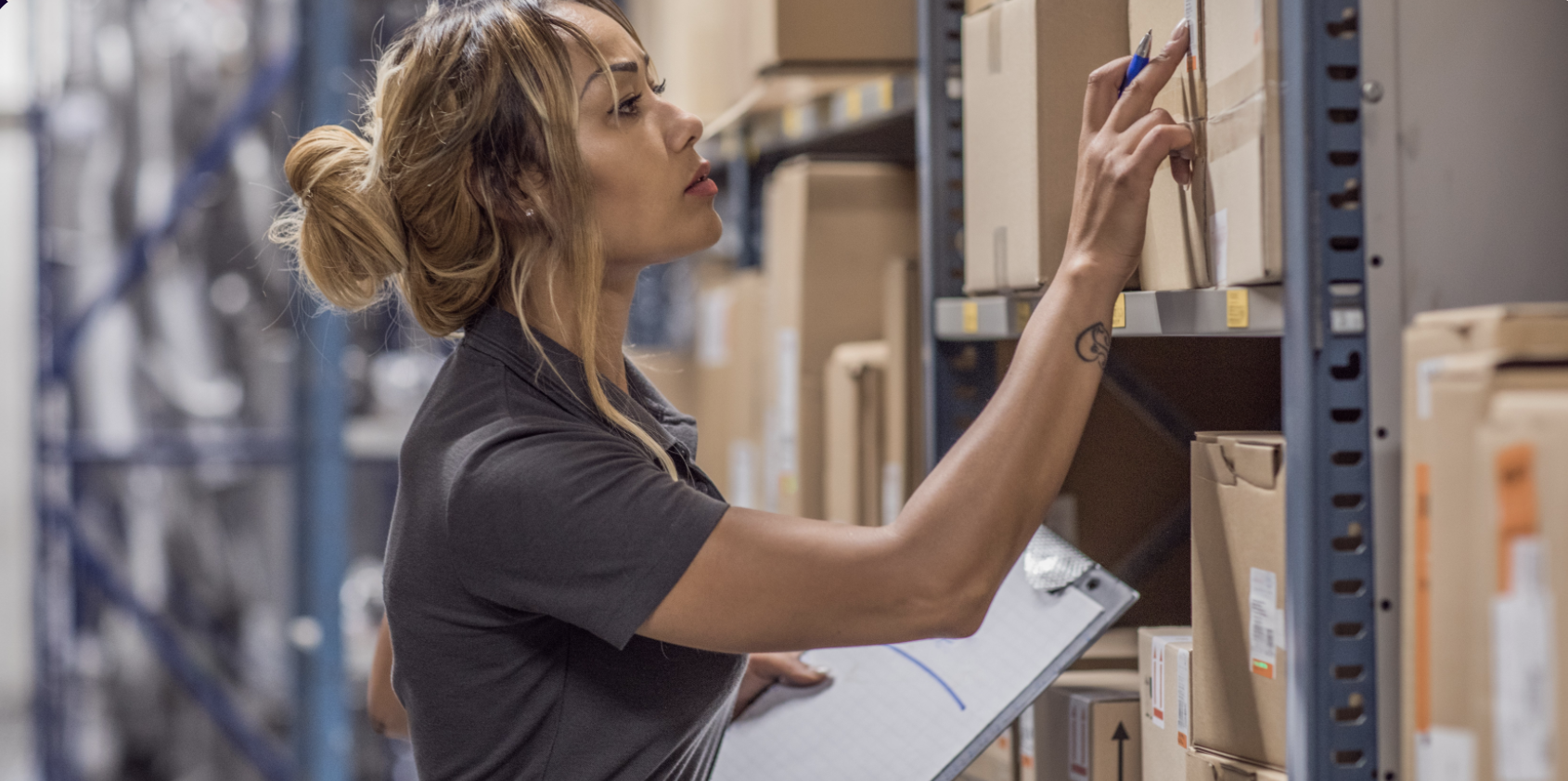 woman standing in warehouse checking a package
